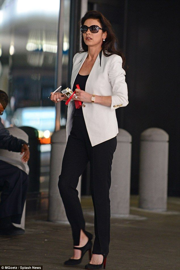 Still smoking: Catherine Zeta-Jones lit up a cigarette while waiting for her husband at the airport