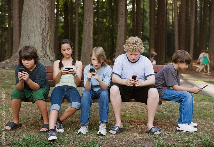 Boys and girls (10-11) using mobile phones in forest by Andersen Ross Photography communication!