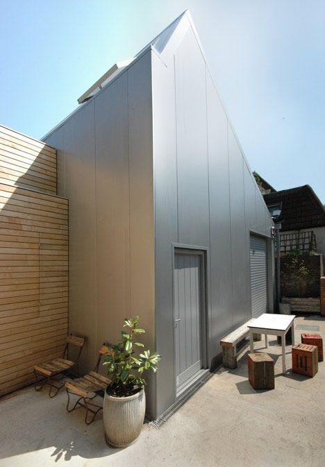 Hoxton architects Edgley Design tucked this rubber-clad residence and aluminium artist's studio behind a row of semi-detached houses in Hackney.