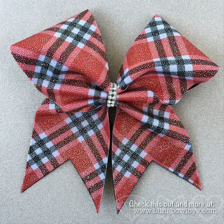 "Red & black plaid with an overlay of iridescent shimmer to make this bow sparkle. Great for any sport including cheer, softball, basketball, soccer, or volleyball. Bow measures 8"" x 8"" with a rhinesto"