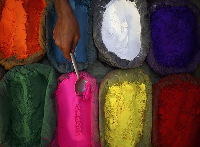 A vendor in Kathmandu sells powder dyes used for worship during Tihar, a five-day festival that incorporates Diwali