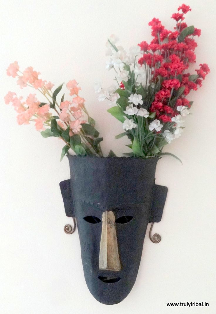 Wall-mounted Mask n Vase  Handcrafted Wrought-iron Mask n Vase, by artists from Baster Region. An beauty with difference, will match well with any kind of decor, Modern or contemporary or traditional decor. Can use inside the house or at outdoors. Masks are considered to bring good luck to the place  Can be used as plin mask on the Wall or can put fry flowers to enhance its beauty.   Size (Inches) : 10x8  Weight (gms): 350 gms