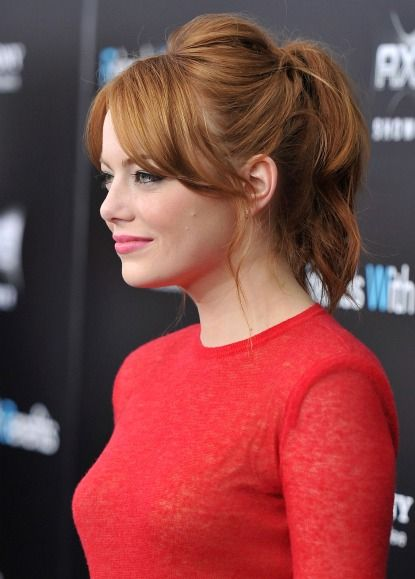 Emma Stone's ponytail hairstyle. The key components of this hairstyle includes cool long bangs parted in the middle, long loose wisps in front of ears, and a crown that's been teased and pushed forward to add a fun bump of volume up top. The easiest way to copy this ponytail? Use a barrette to secure the top section of your hair first, holding the bump in place, and then pull the rest of your hair into a high pony.