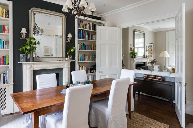 Dining room with white slipcovered parson chairs, farm table, and fireplace. Interior Design by Imperfect Interiors. Photo: Chris Snook.