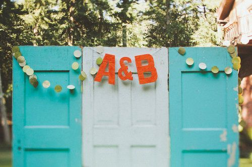 The thought behind this backdrop is simple but so charming: painted doors with vibrant pops of color from the couple's initials.  Photo by Paige Jones Photography via Style Me Pretty