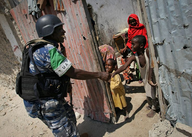 A Ugandan police officer serving as part of a Formed Police Unit (FPU) with the African Union Mission in Somalia (AMISOM) shakes hands with a young Somali boy during a foot patrol in the Kaa'ran district of the Somali capital Mogadishu 09 November 2012. AMISOM's FPUs are working with their counterparts in the Somali Police Force (SPF) in helping to provide security in Mogadishu in addition to training and mentoring the SPF on policing techniques and practises. AU-UN IST PHOTO / STUART PRICE.