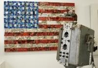 """Quelques unes de ses oeuvres sont visibles à la Galerie Brauer [ Recycl'art et Upcycling ] dans le Marais à Paris. Ici on aperçoit """"Flag"""", derrière un robot de Thierry Deroche."""