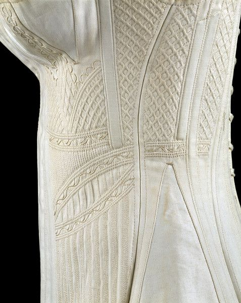 England, ca. 1825 - 1835  Cotton, silk thread, trapunto work;  White cotton corset with silk trapunto work. Busk down centre middle, separate breast double-gussets with trapunto strap in centre of each breast. Corded and quilted work down sides of corset, armholes set quite far back. Laces down the back