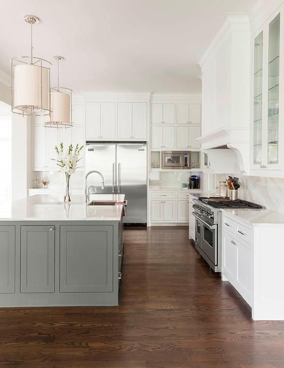 A pair of fabric and metal cylinder pendants hang over a gray kitchen island fitted with a sink, ...