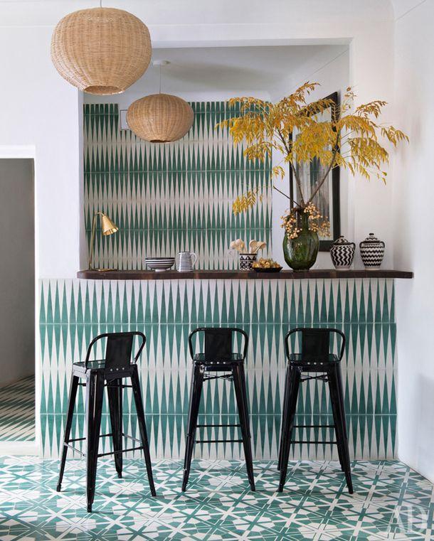 Дом во Франции. Металлические барные стулья, бирюзовый повторяющийся орнамент и плетеные плафоны светильников делают эту кухню похожей на бар на берегу моря.