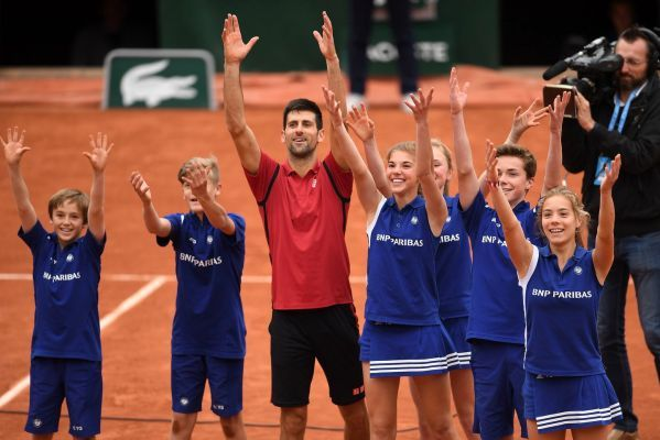 Novak Djokovic celebrates victory with the ballkids during