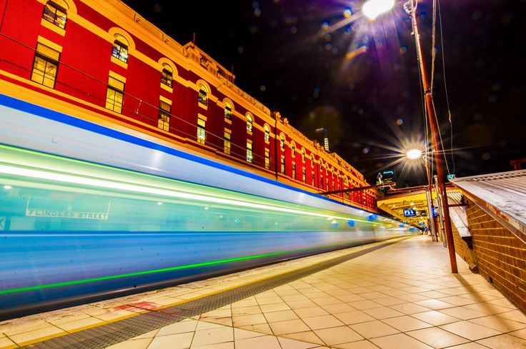 A blue & green-colored Public Transport Victoria train passing by one of Melbourne's landmarks, Flinders Street Station. The Station is Australia's oldest train station and is today the busiest suburban railway station in the Southern Hemisphere with over 1,500 trains and 110,000 commuters passing thru each day. August 2017. #flindersstreetstation #ptvictoria #publictransportvictoria #melbournecity #victoria #australia #nightphotography @railways_of_our_world #railwaystation