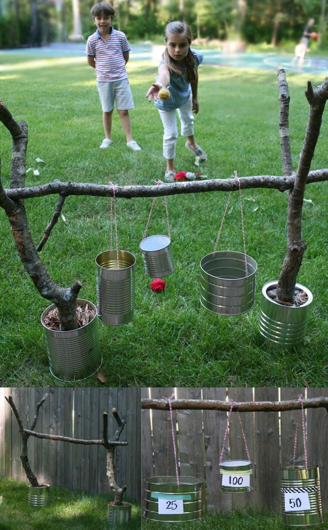 """BALL TOSS GAME: Set two tree branches (with a """"V"""" on the top) into cans and fill with rocks, sand, or mulch. Place a straight branch across the top & set it inside the """"V"""" of the support branches. Punch two opposite holes, into different size cans, and thread yarn or string thru the holes and tie to the straight branch at varying heights. Label varying size cans with point values (smaller cans=more points). Add a throwing line.Toss yarn or other balls into cans & see who can score highest!"""