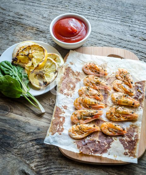 Shrimps with lemon and spicy sauce on the wooden background royalty-free stock photo
