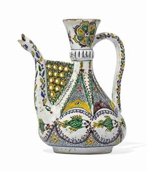 A KUTAHYA EWER 19TH CENTURY Rising from short foot through rounded body tapering to thin neck with pronounced collar and terminating in flaring mouth, curved handle and spout with snake's head finial with openwork lattice between the base of the spout and the body, the white ground painted in yellow, manganese, green, bole-red and blue, with a series of geometric and floral patterns and a band of stylised fish below, Armenian inscription on either side of the