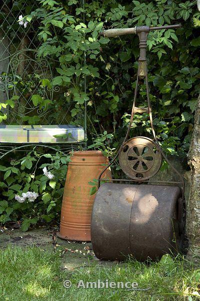 Angolo di giardino di periferia con sedia imbottita, cotto rabarbaro forcer e antico rullo da giardino in metallo contro la recinzione di filo spinato recinzione giardino coperto di piante rampicanti