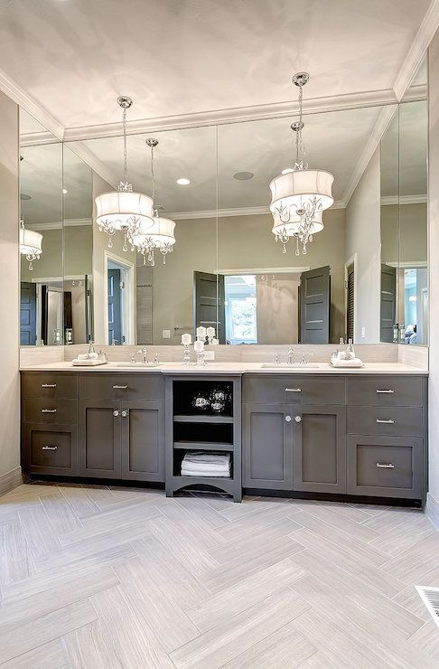 Muted grey vanity with polished nickel pulls and a light stone counter, wraparound mirror, crystal drum chandeliers, light gray herringbone tiled floors.