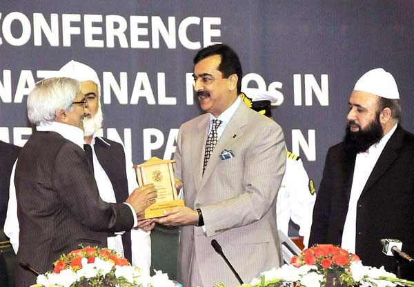 ISLAMABAD: April 23 - Prime Minister Syed Yusuf Raza Gilani giving award to Munu Bhai at the National Book Day function at Pak-China Friendship Centre.