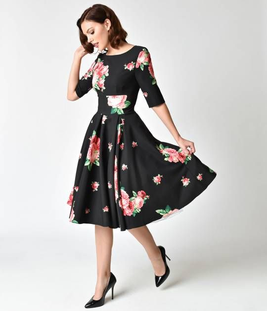 Its time to smell the roses, dear! This delightful frock from The Pretty Dress Company brings you the Hepburn Swing Dress in a cheerful 1940s inspired black and pink floral print, cast in a classic retro dress design! Lovely details include a chic high b