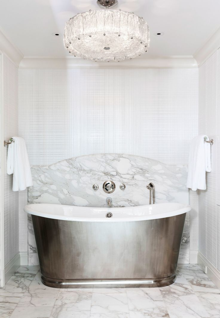In a master bathroom, a slab of dramatically veined Calacatta Borghini marble covers the wall behind the soaking tub | archdigest.com