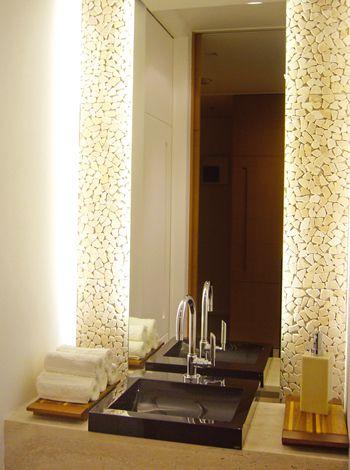 Backlighting has a nice effect on the pebble backsplash of this modern bathroom.