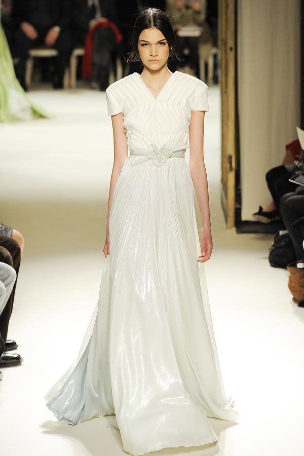 Schon fast futuristisch: Dieses Hochzeitskleid von Georges Hobeika Haute Couture ist etwas für Individualistinnen! Das Oberteil kommt mit einer grafischen Fältelung und geht in einen zart türkis/blau schimmernden, schwingenden Rock über. Ein Blumengürtel im japanischen Stil komplettiert dieses besondere Hochzeitskleid.