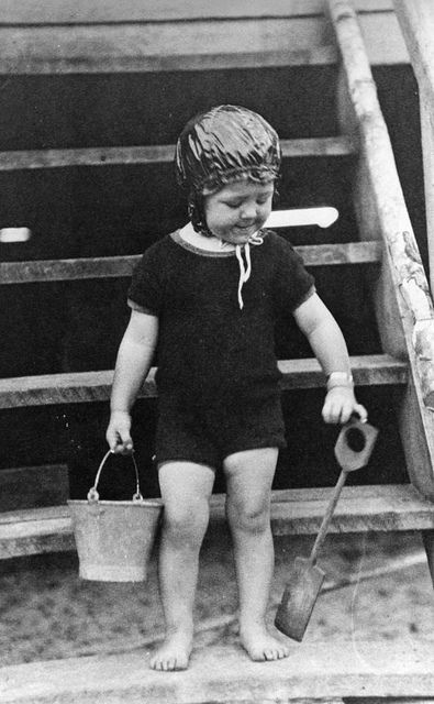 Young child in swimming costume with bucket and spade.