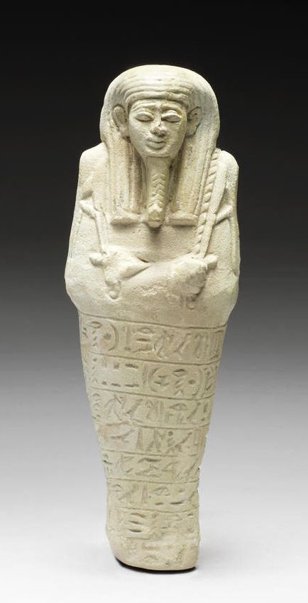 An Egyptian pale green glazed composition shabti for Wawawer  Late Period, 26th Dynasty, circa 664-525 B.C. Of typical mummiform shape, wearing the tripartite wig and the false beard, holding the pick, the hoe and a twisted rope holding the basket behind the left shoulder, inscribed with seven horizontal lines of hieroglyphs, 6¼in (16cm) high