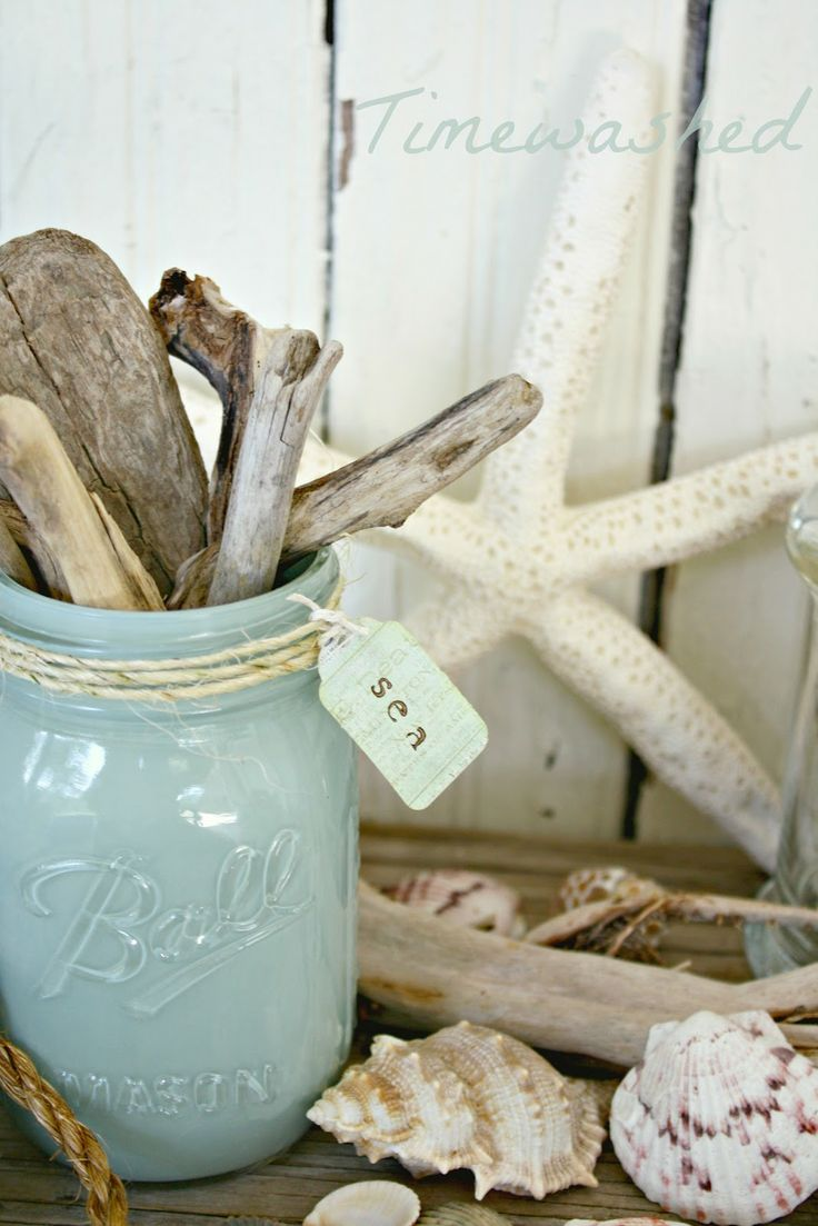 A painted mason jar holds found driftwood pieces. Starfish and scattered sea shells create a beach vignette on a foyer table.