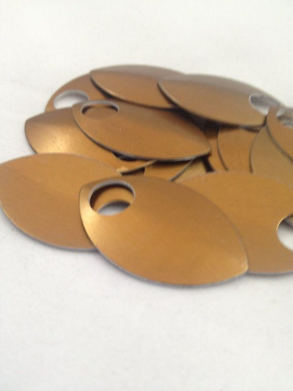 This listing is for 100 Bronze Large anodized aluminum scales. They are perfect for use in making scalemaille (scale mail) for armor and also