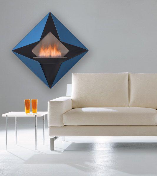 DIAMOND Camino da parete. Design ispirato al diamante, geometrie pure. Realizzato in metallo verniciato nero e i quattro triangoli in argento metallizzato o nei colori della gamma ALTRO FUOCO.