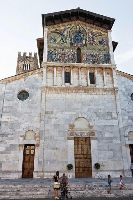 Lucca, Toscana, Italy- Basilica di San Frediano. Fin dal VI secolo esisteva in questo luogo un edificio religioso, la cui costruzione si fa risalire allo stesso San Frediano, vescovo di Lucca tra il 560 e il 588. Nel 1112 iniziò la riedificazione dell'edificio che fu consacrato nel 1147. La chiesa era più bassa di quella che oggi vediamo; il rialzamento data al XIII secolo e venne concluso con l'ornamentazione a mosaico della parte superiore della facciata.