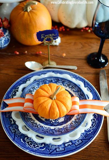 A bold color combination of blue and orange is displayed with layered dinner plates, a striped ribbon, and miniature pumpkins.