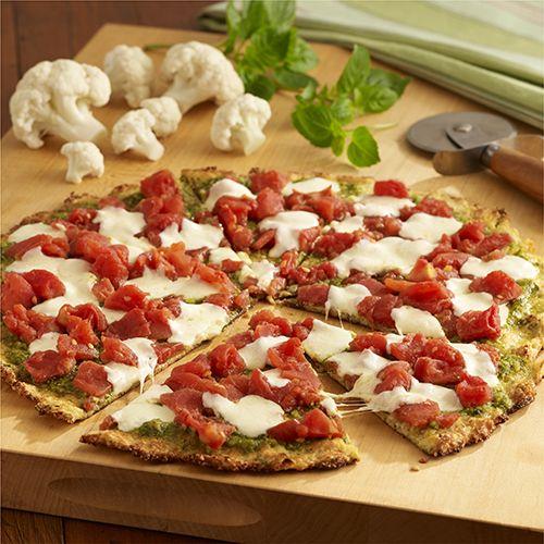 PIZZA DE CORTEZA DE COLIFLOR CON PESTO Y TOMATES         Una pizza baja en carbohidratos preparada con corteza de coliflor, pesto de albaha...