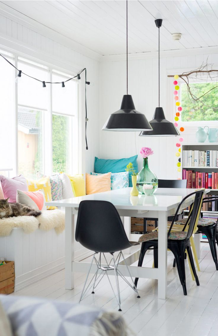 Inject colour into a black and white colour scheme with brightly colour pillows - like on this bench in a family dining room.