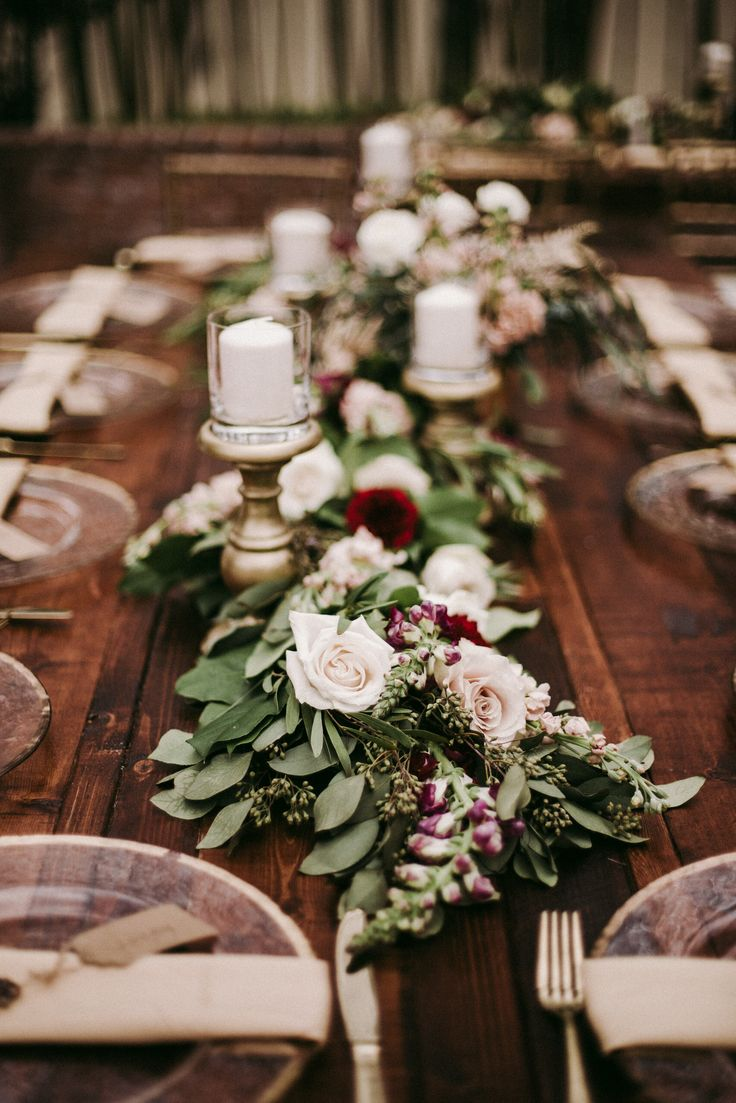 on varnished farm tables, lush garlands of lemon leaf, seeded eucalyptus, willow eucalyptus filled with vendela roses, quicksand roses, white majolik spray roses, burgundy snapdragons, burgundy carnations, peach stock and lined with pillar candles on gold pedestals.