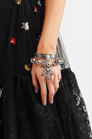 Alexander Mcqueen (UK), antique effect silver and gold tone brass Celtic inspired cuff bracelet, engraved with intricate floral motifs, and has bell charms that are hollow for lightness and glisten with Swarovski crystals. #uk   peculiarjewelry.com