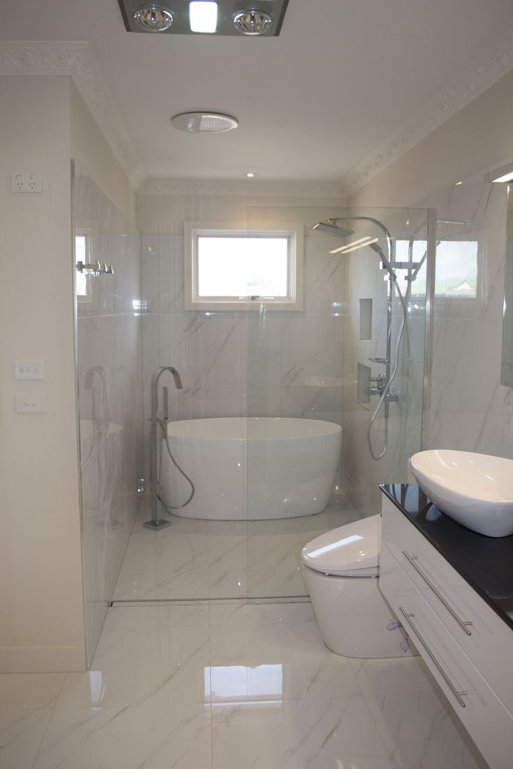 Timeless white bathroom with a frameless and stepless shower is beautifully done in sophistication and style.