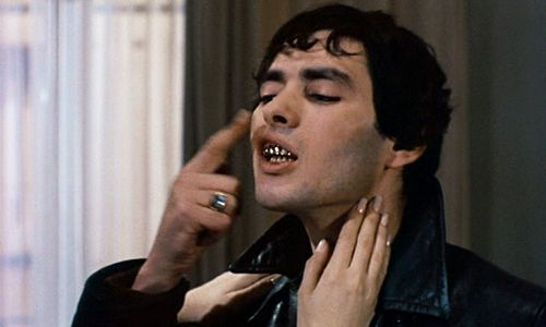 Pierre Clementi as Marcel in Belle de Jour. Marcel, a dark haired man in a black leather jacket, bares his teeth, showing off his shiny metal dentures. He raises a finger to his lips.