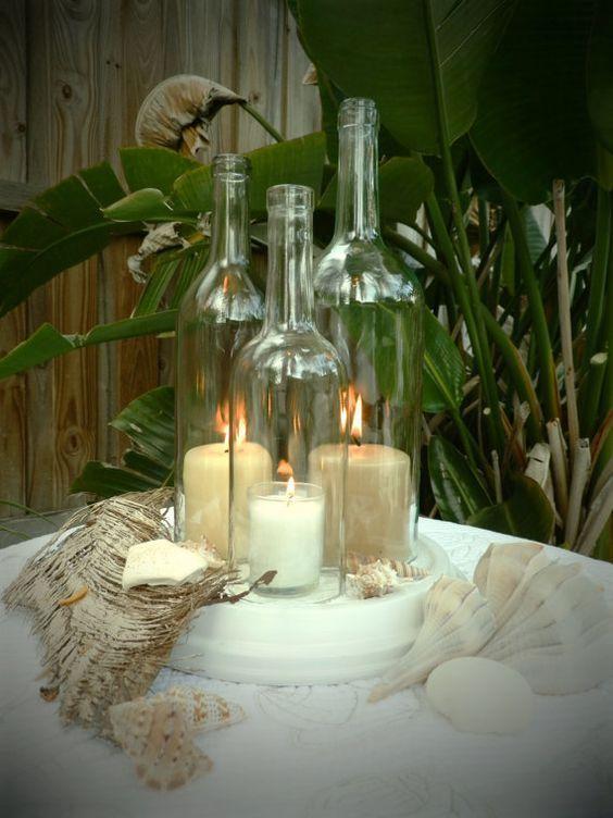 Hermosa botella de vino centro de mesa de lámpara de huracán de arte. Tres reciclan botellas de vino de diferentes tamaños y alturas. Un 1.5 litros claro en 12 Una de 750 ml. claro en 10,75 Una de 750 ml. claro en 9,75 Mano cortada y meticulosamente pulida a un borde super suave. Base de arcilla incluyen está pintado de blanco y diseñado con un patrón de remolino con textura para permitir el flujo de aire así que velas puede respirar. La base es de 10,75 pulgadas de diámetro. Excelente ce...