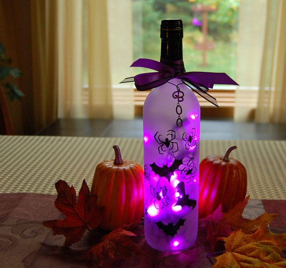 This Halloween light features black bats and spiders and purple lights. It was created from a recycled wine bottle. The wine bottle was