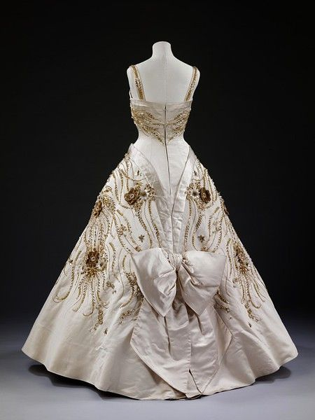 "c. spring/summer 1957, English ""The Flowers of the Fields of France"" by  Norman Hartnell of Duchesse satin, embroidered with pearls, beads, brilliants and gold thread. Worn by Queen Elizabeth II on a state visit to Paris in 1957. V"