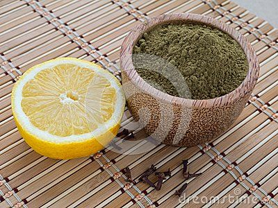 Henna powder in coconut bowl,lemon and cloves on the bamboo mat