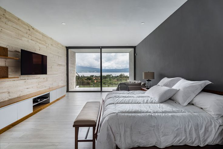 In this modern bedroom a board formed concrete wall sits opposite a dark grey accent wall, and both of them flow through to the exterior of the house. A sliding glass door opens the bedroom up to a private balcony with views of the neighborhood. #ConcreteWall #ModernBedroom #BedroomDesign