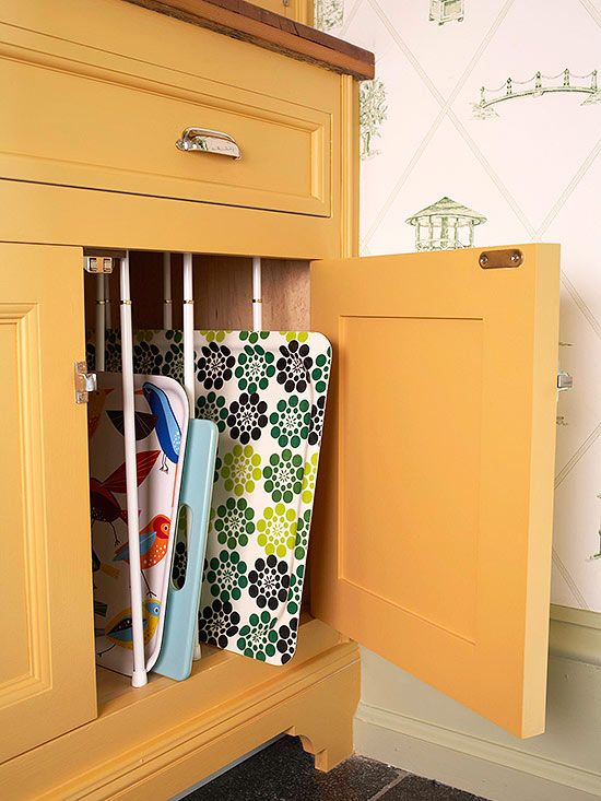 Create a vertical partition in a cabinet with pairs of spring-loaded curtain rods to keep baking sheets, platters, cutting boards, and trays in line.