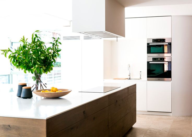 Travertine floors, and a mix of warm oak timber clad and white painted walls create a warm, welcoming charm, while lacquered modern kitchen cabinets combined with oak kitchen island and a white quartz countertop. Sydney based design firm C + M Studio