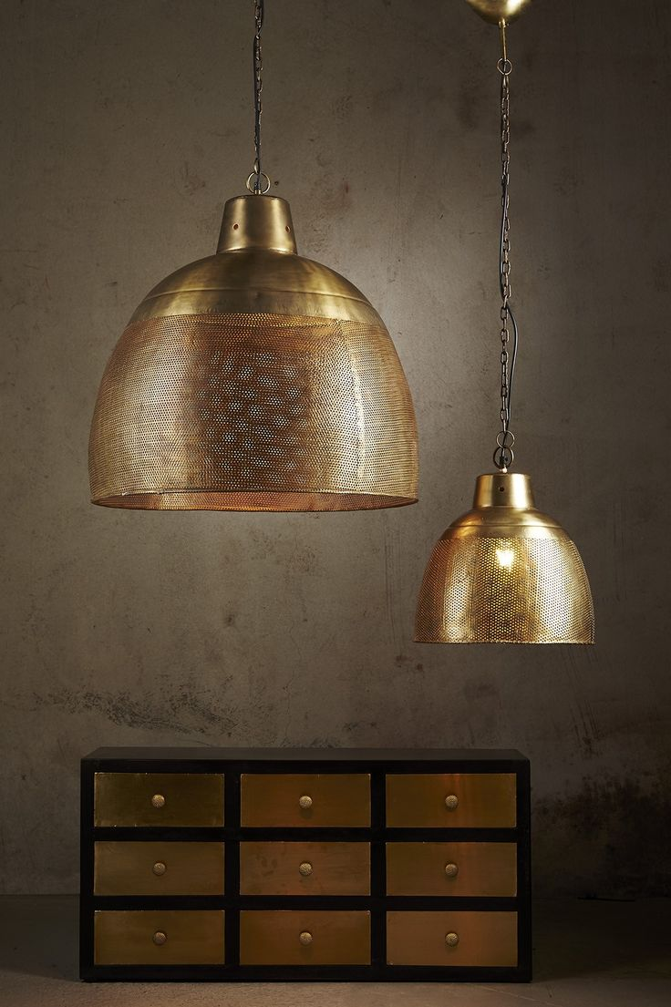 A brass perforated pendant light with an antique gold appearance . This pendant is designed to patina over time for a vintage aesthetic.