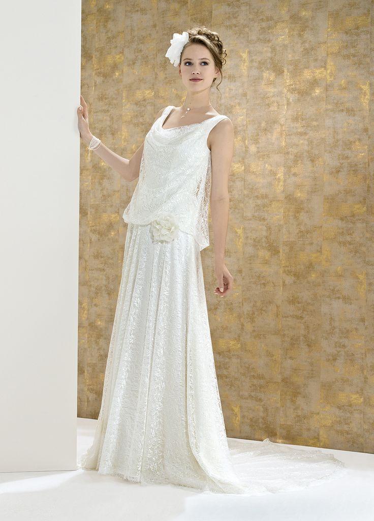 Allure vintage et style bohème.  Cette robe de mariée à bretelles en dentelle chantilly s'exprime en souplesse jusqu'au bassin, rehaussé d'une rose. La jupe est tout en fluidité.    Robe en dentelle col bénitier - Fermeture et boutons au dos