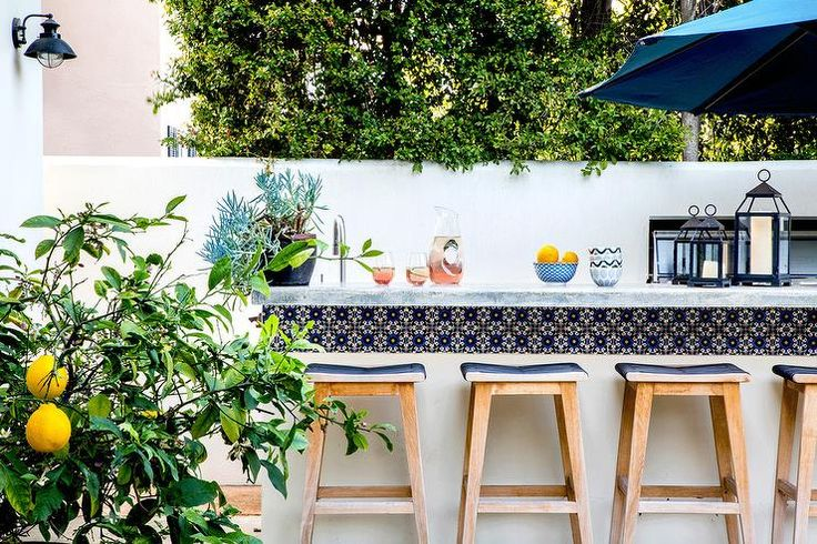 Malibu Spanish Tiles trim an outdoor island bar paired with crate and barrel backless wooden stools with blue upholstered seating.