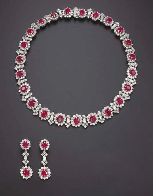 A SUITE OF RUBY AND DIAMOND JEWELRY   Comprising a necklace, set with twenty-three slightly graduated oval-cut rubies, each within a circular-cut diamond surround, enhanced by circular and marquise-cut diamond intersections; and a pair of ear pendants en suite, mounted in 18k white gold, necklace 15 ins.  The total weight of the rubies and diamonds is approximately 59.50 and 38.00 carats